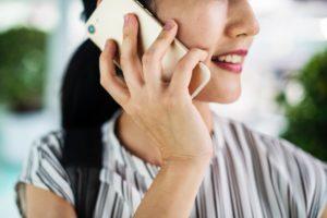 地方自治体の事務職の女性が携帯電話で通話中